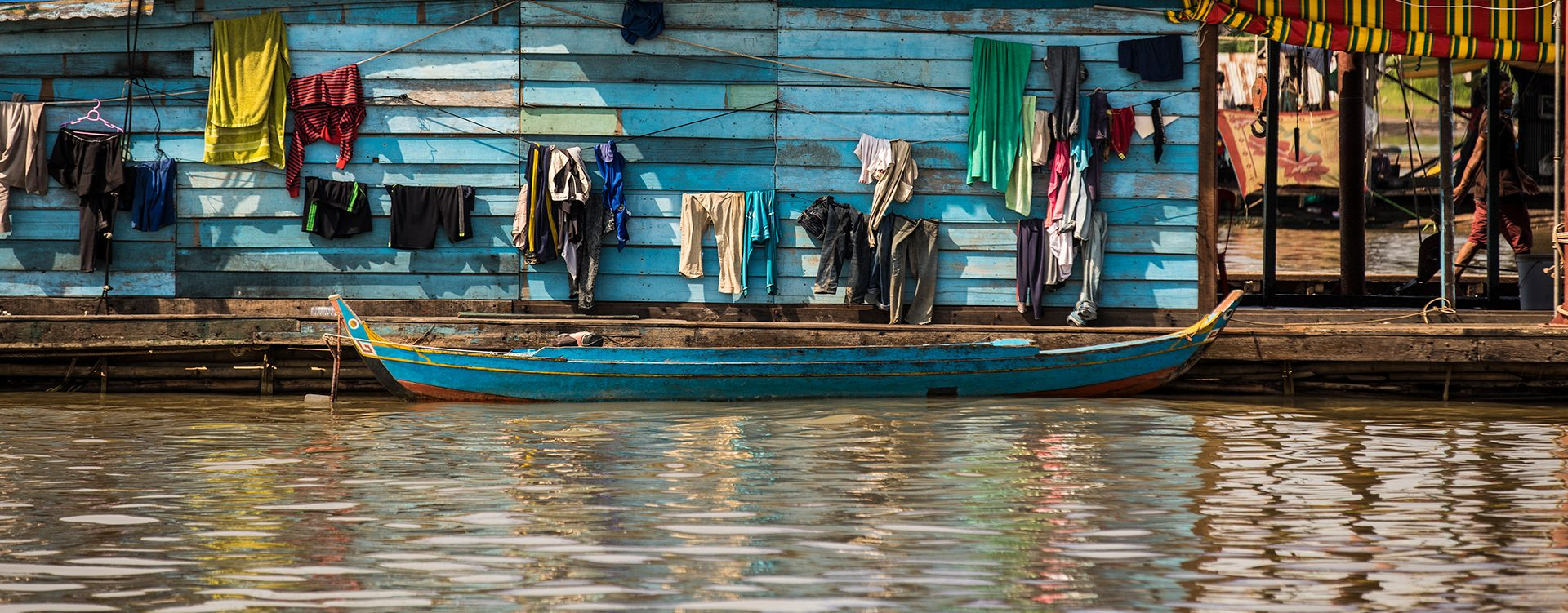 Image of a small boat and clothes hanging on a house on the Mekong River in Cambodia